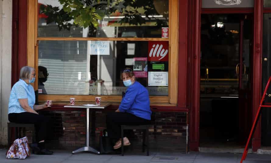 two women sitting apart outside a coffee bar