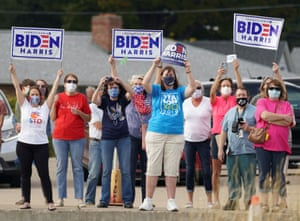 Supporters hold signs as they await the arrival of Joe Biden in Erie, Pennsylvania, on 10 October.