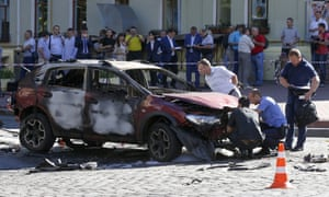 Police examine the wreckage of the car that Pavel Sheremet was travelling in