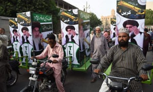 Supporters of Tehreek-e-Labbaik, which promotes the death of blasphemers, ride with election posters in Karachi