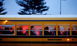 People arrive on a school bus at Newtown High School for a memorial vigil after the 2012 Sandy Hook shooting.