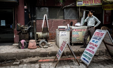 A shopkeeper stands next to a generator outside a commercial complex in Nehru Place, New Delhi