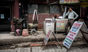 A shopkeeper stands next to a generator outside a commercial complex in Nehru Place, New Delhi, India.