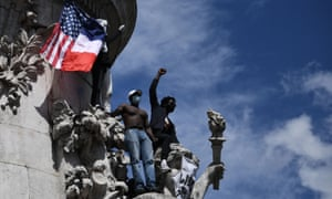 Protesters raise their fists from the statue of Marianne on Place de la Republique in Paris on Saturday.