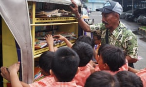 A man allows young schoolchildren to pick out books from shelves on the back of his rickshaw.