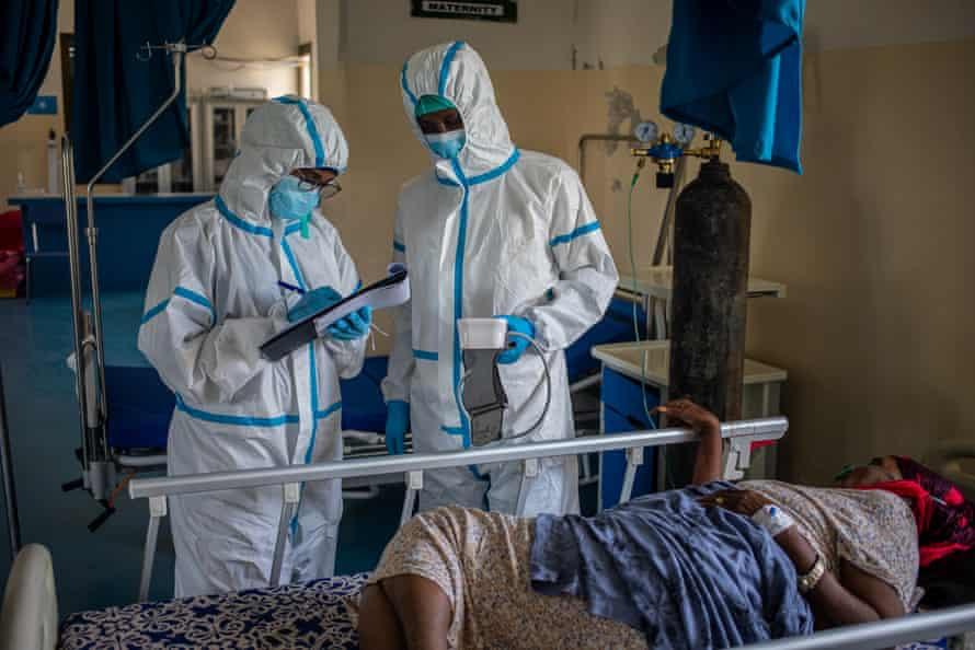 Medical staff take a patient's temperature before testing her for coronavirus at De Martini hospital.