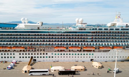Medical personnel tend to passengers as they disembark from the Grand Princess cruise ship at the Oakland port.