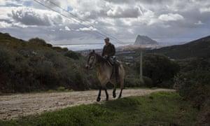A man on a horse with the Rock and La Línea de la Concepción in the background