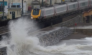 Waves crash against the seafront and railway line in Dawlish, Devon, UK.