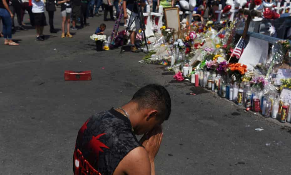 A man prays at a memorial three days after a mass shooting at a Walmart store in El Paso, Texas.