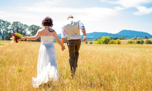 Bride and groom walking together on their wedding day through a field.