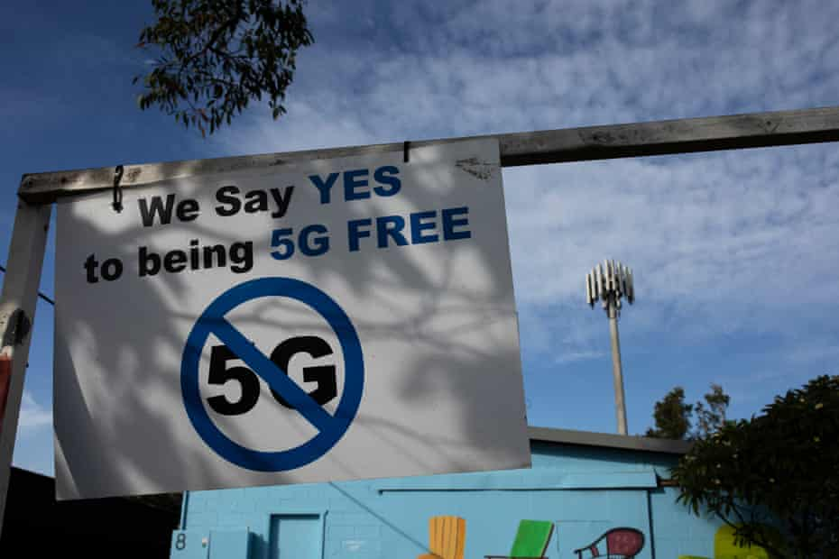 Anti-5G signage at a Telstra exchange facility in Byron Bay with the Telstra transmission tower seen in the background.