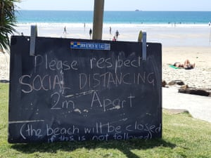 A sign warns beachgoers in Byron Bay to practice social distancing