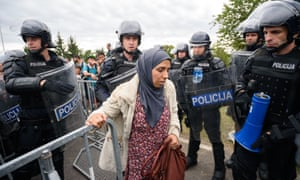 Slovenian police allow refugees to enter the country through the border crossing in the Croatian village of Harmica.