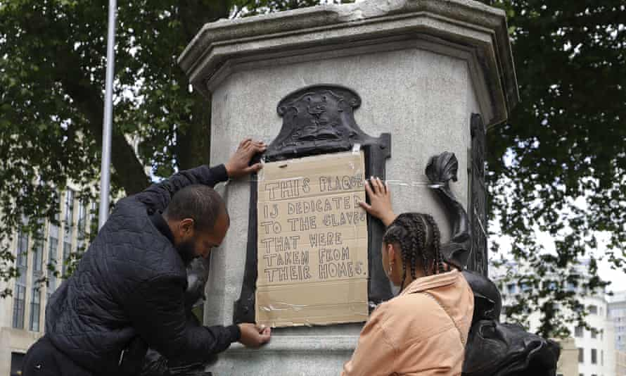 A banner is taped on the pedestal of the toppled Edward Colston statue.