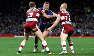 Warrington Wolves' Josh Charnley is tackled by Wigan Warriors' Dan Sarginson (left) and Liam Farrell.
