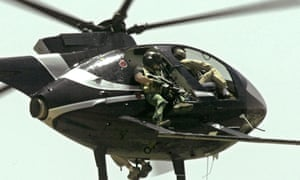 Members of Blackwater security contractors fly a Hughes 500 helicopter over the Tigris river in Baghdad on 5 May 2004. The security firm was contracted by the US government to provide security to US officials in Iraq.