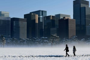 Tokyo, Japan: People walk in snow near the Imperial Palace