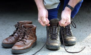 To the right a man ties up a pair of walking boots - only his hands and feet visible.  To the left a pair of lighter walking boots.