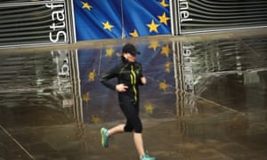 A woman jogs outside the European Commission headquarters in Brussels