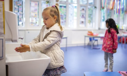 Socially distanced children washing hands in classroom