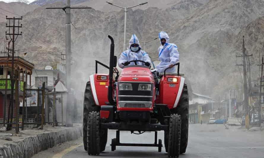 Health workers wearing protective gear ride a tractor as they sanitise a street with disinfectant amid the coronavirus pandemic in Leh, India.