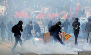 Tear gas floats around masked protesters as they clash with police during May Day protests.