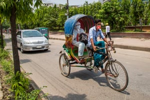 One of the estimated one million drivers of Dhaka cycles with a masked passenger.