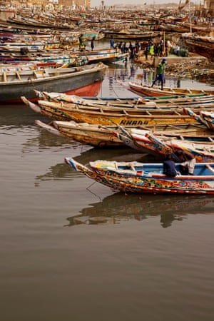 Fishermen moor their boats on a narrow stretch of the Senegal River