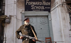 An armed Pakistani policeman stands guard outside a school in Peshawar