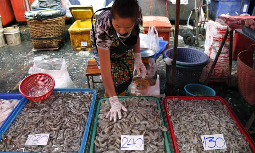 A fish-seller sorts shrimp at Klong Toey market in Bangkok. Activists claim that government measures have failed to end labour abuses in Thailand's seafood industry