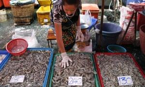 A female worker sorts shrimp at Klong Toey fresh food market in Bangkok