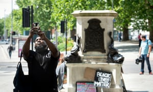 A man poses for a selfie at the site of the toppled statue of Edward Colston in Bristol