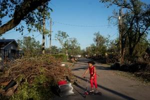 Girl plays near fallen trees