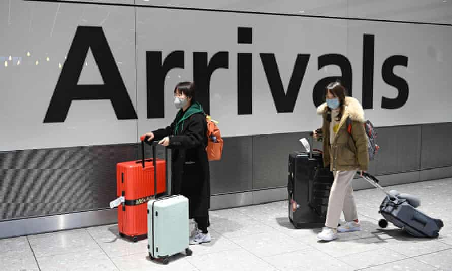 Passengers in face masks arrive at Terminal 5 of London Heathrow airport