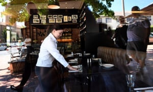 A waitress sets up a table in a restaurant