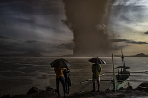 Residents watch the Taal volcano erupting  in Talisay
