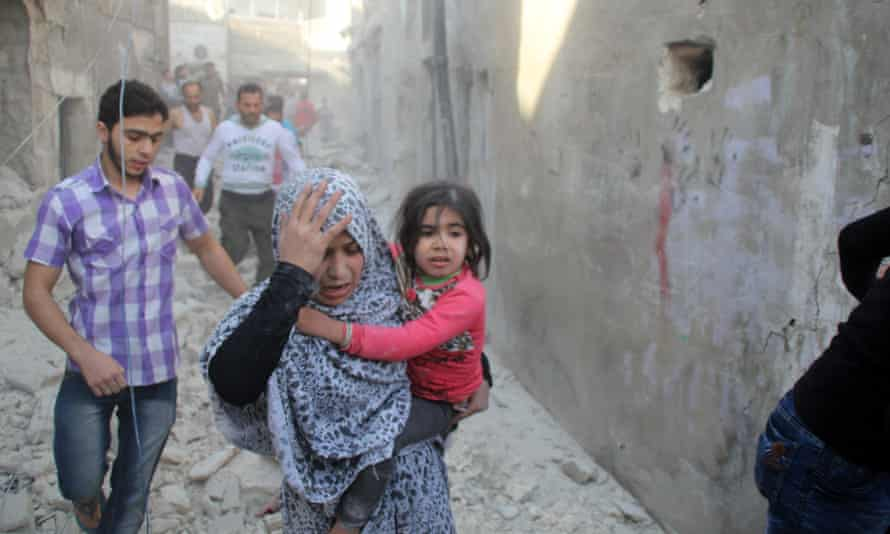 A Syrian woman carries her child as she searches for her relatives in the rubble of destroyed houses following what local activists said was an airstrike by Russia in the rebel-held area of Kallasah on the outskirts of Aleppo, on 30 October.