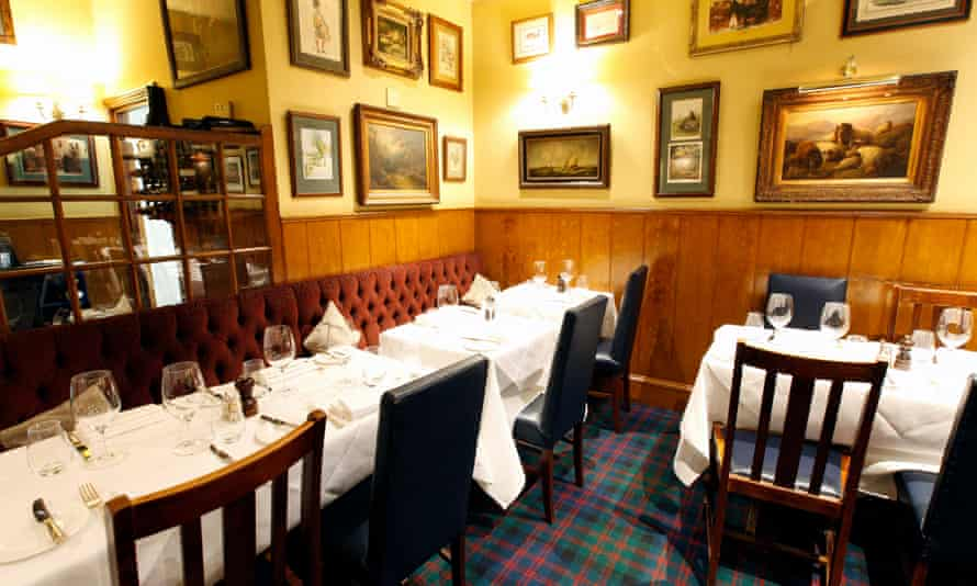Half-panelled walls, tableclothed tables and a velvet-covered banquette