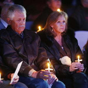 Carl, left, and Marsha Mueller hold candles at a memorial in honor of their daughter Kayla Mueller.