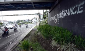 Motorists in Yogyakarta pass by graffiti calling for tolerance amid an increase in verbal attacks on the LGBT community.