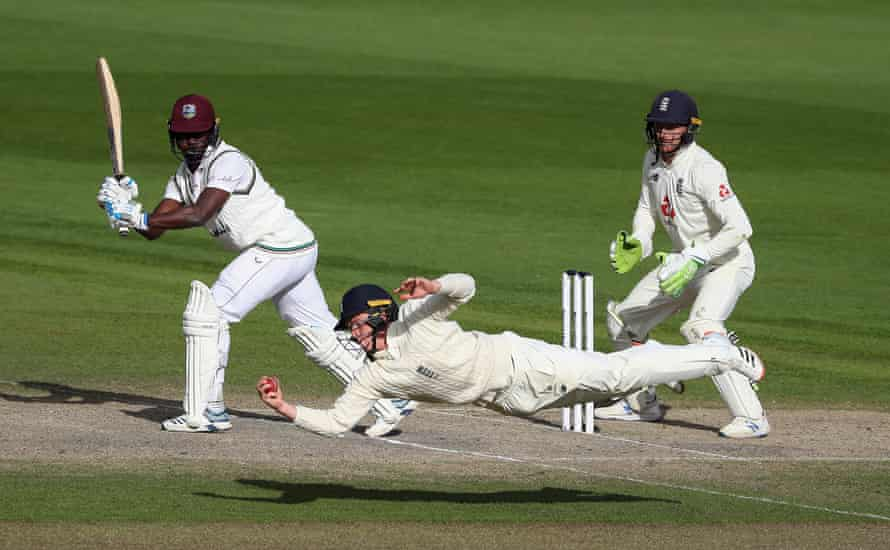England's Ollie Pope dives to catch out Kemar Roach of West Indies to win the match during the fifth day of the second Test at Old Trafford on 20 July.