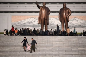 A family walk down the steps after paying their respects before the statues of the late North Korean leaders