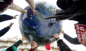 Climate protesters wield a globe-shaped balloon during a rally at the start of the 2015 Paris World Climate Change Conference