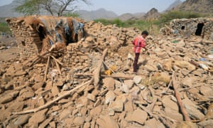 A boy walks on the rubble of houses destroyed by Saudi-led airstrikes in Yemen