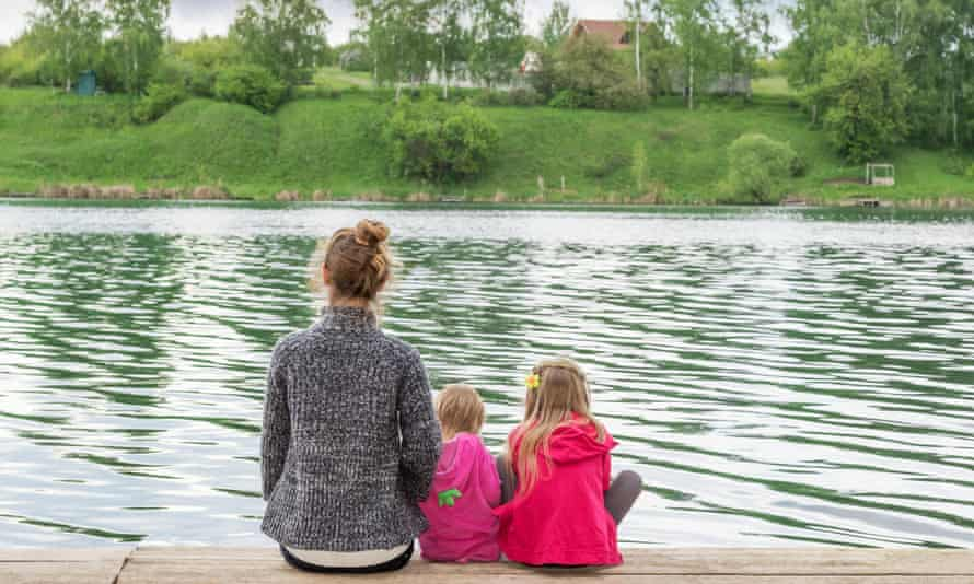 Mother with two daughters on a wooden board on the shore of lake rear view