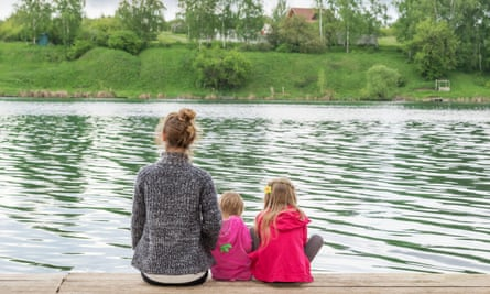 Mother and two small children sitting by a lake