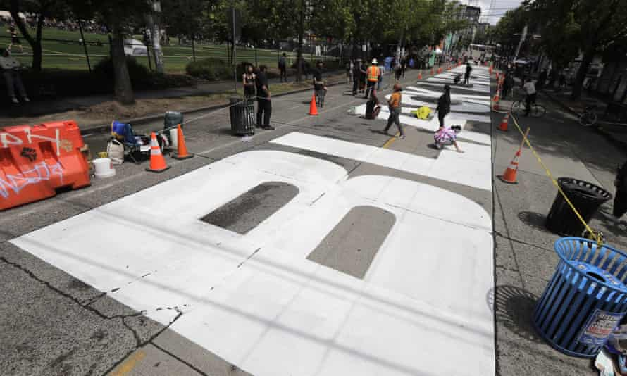 People work to dry off large letters that read 'Black Lives Matter' in the area.