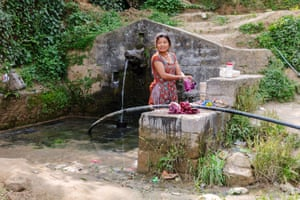 A young woman washes her clothes in a spring in Dhulikhel, Nepal.