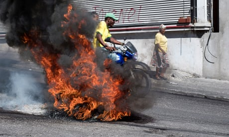 A motorcycle passes a roadblock of burning tyres near Port-au-Prince's Toussaint Louverture airport during demonstrations against the government of President Jovenel Moïse